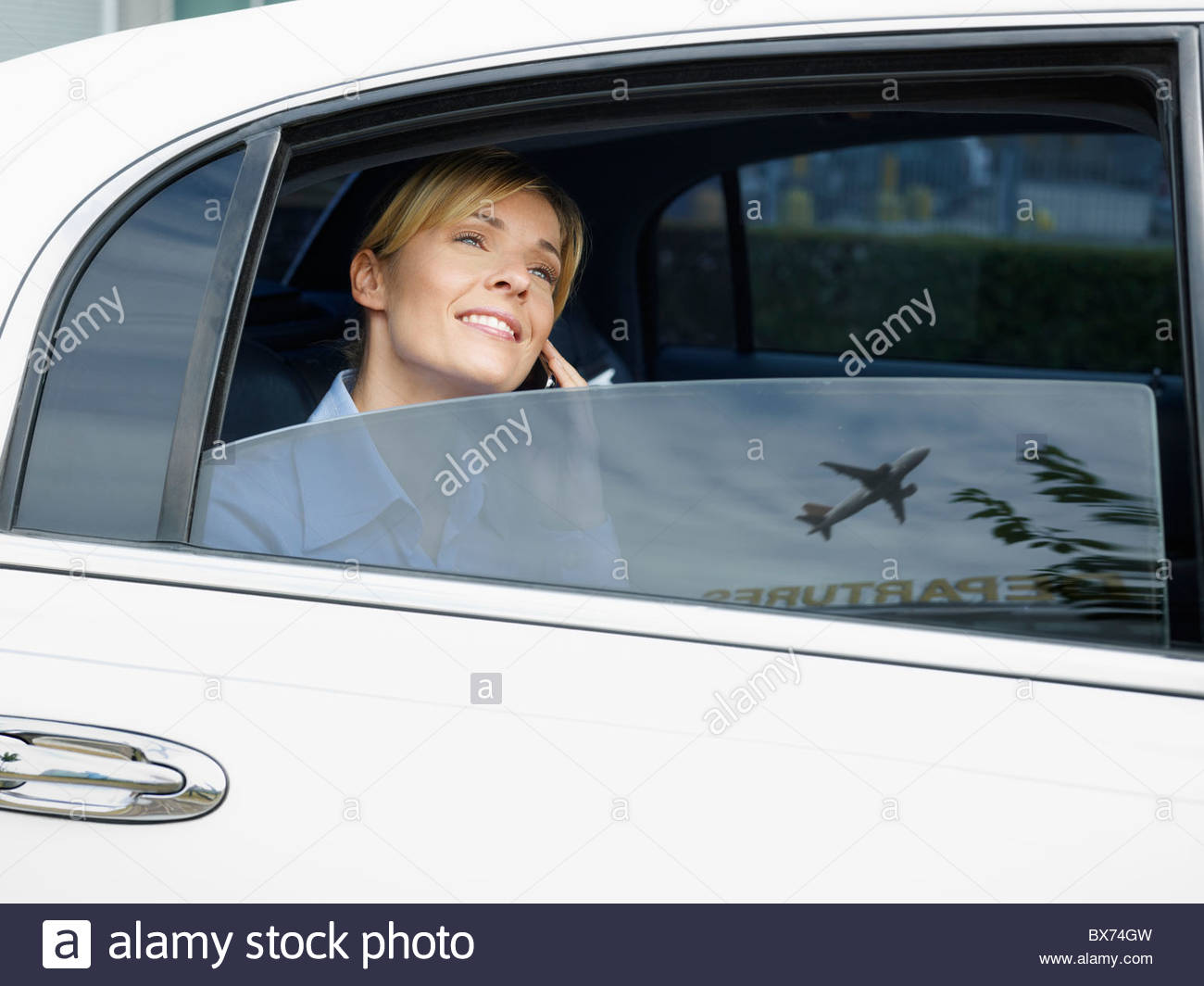 Businesswoman in limousine at airport - Stock Image