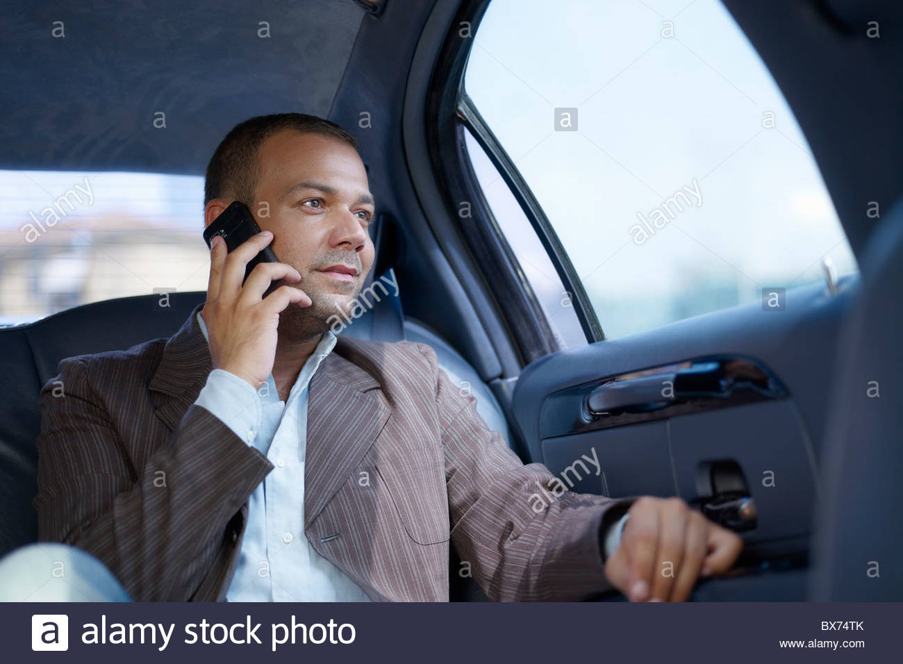 Businessman on the phone in limousine - Stock Image