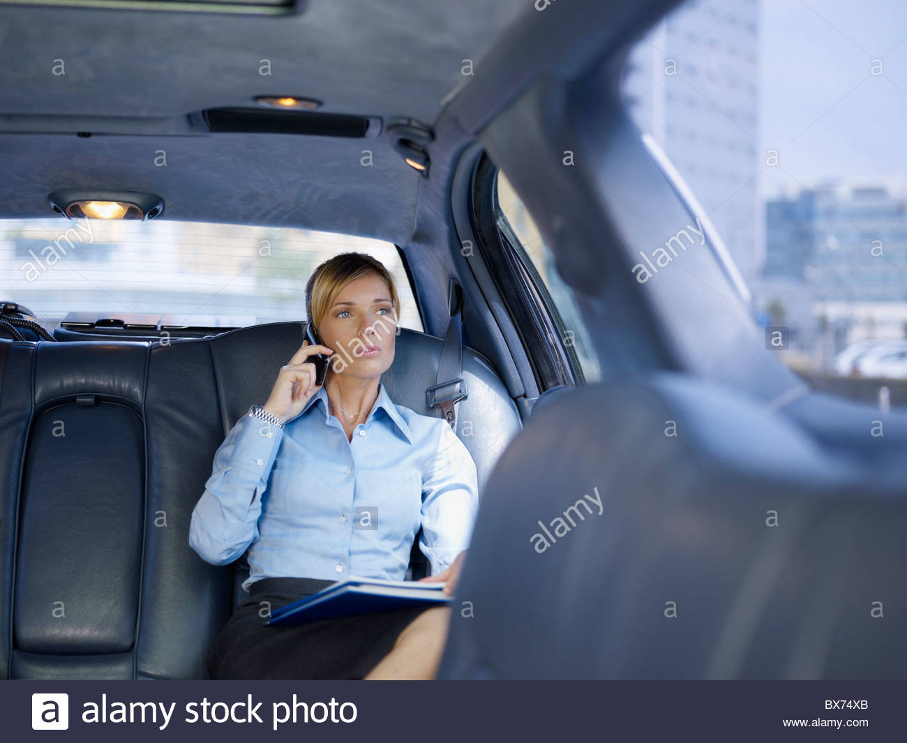 Businesswoman with phone in limousine - Stock Image