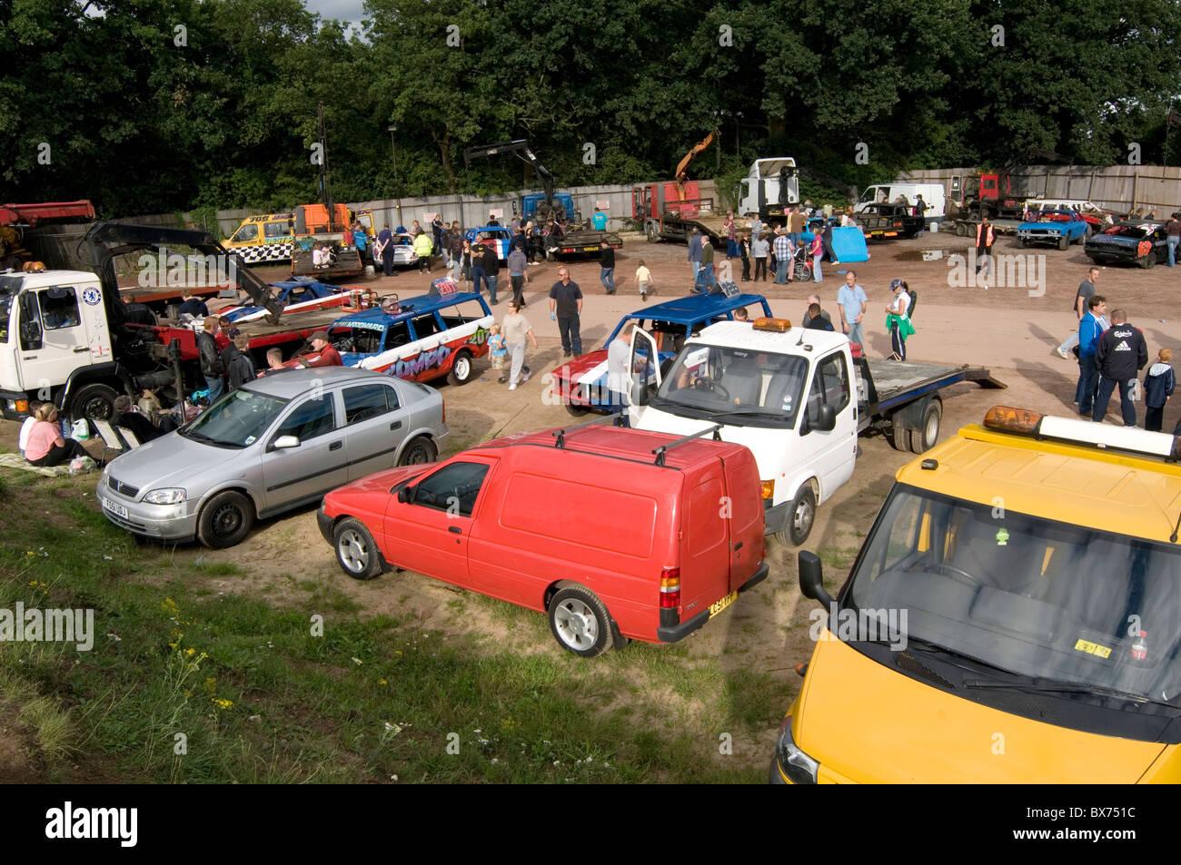 in the pits at stock car race races racing meeting scene repair repairs repairing banger racing car cars truck lorry - Stock Image