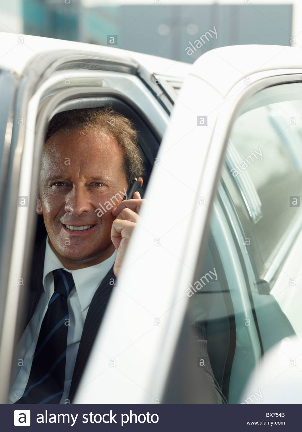Driver on the phone in limousine - Stock Image