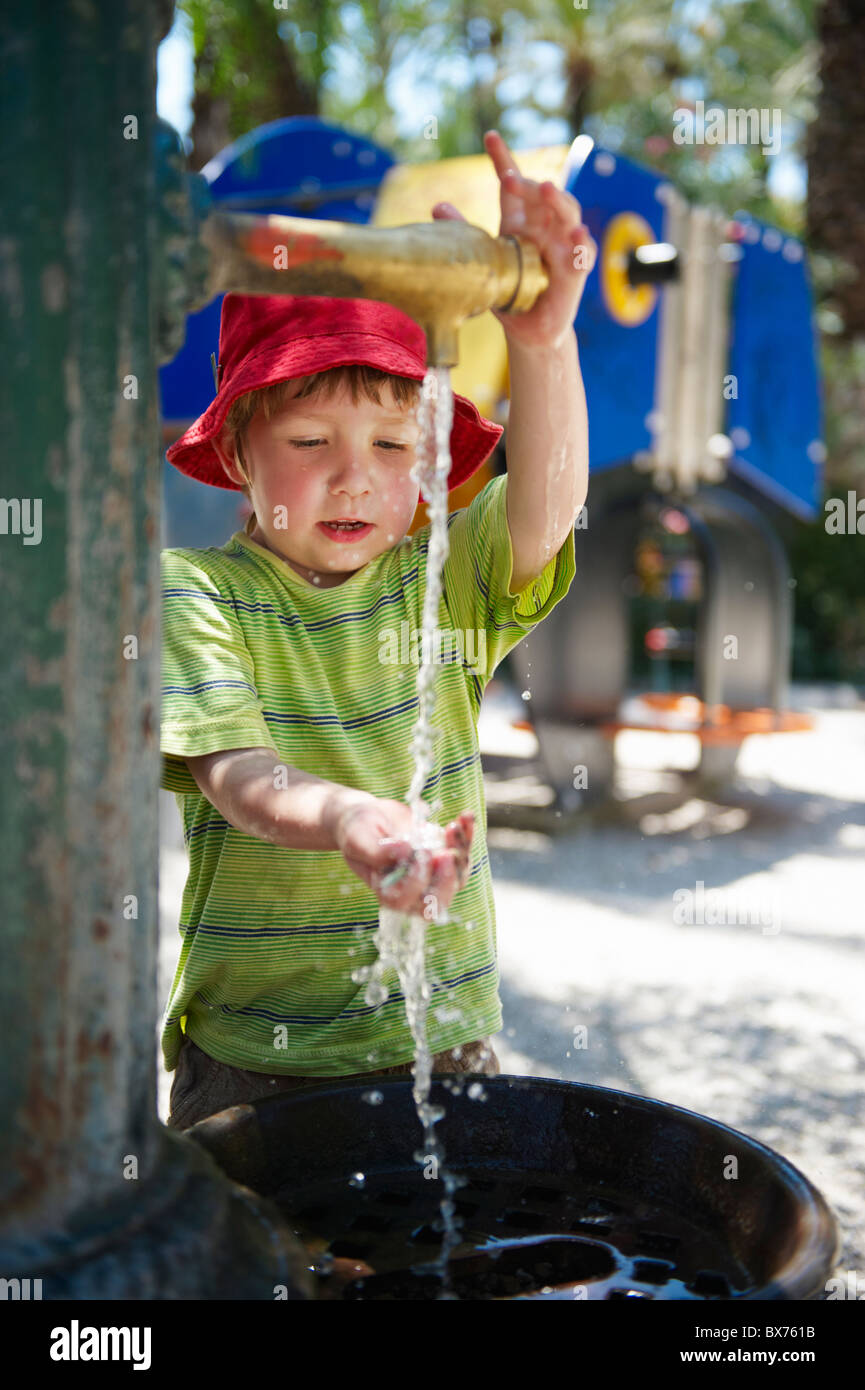 Young boy washing his hand in water fountain outside in playground - Stock Image