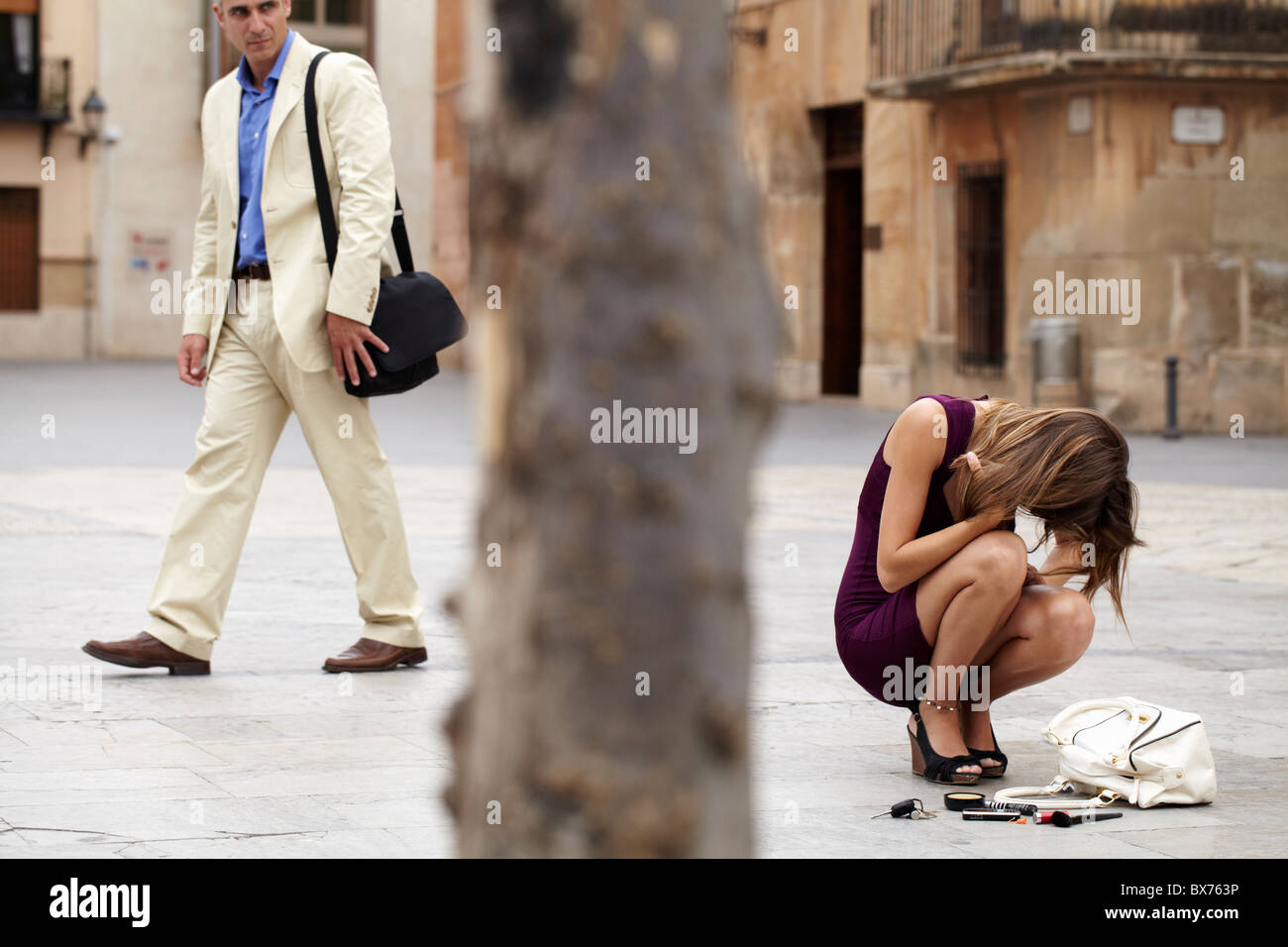 Woman crying over contents of handbag spilt on the street, older man walking by looking at her - Stock Image