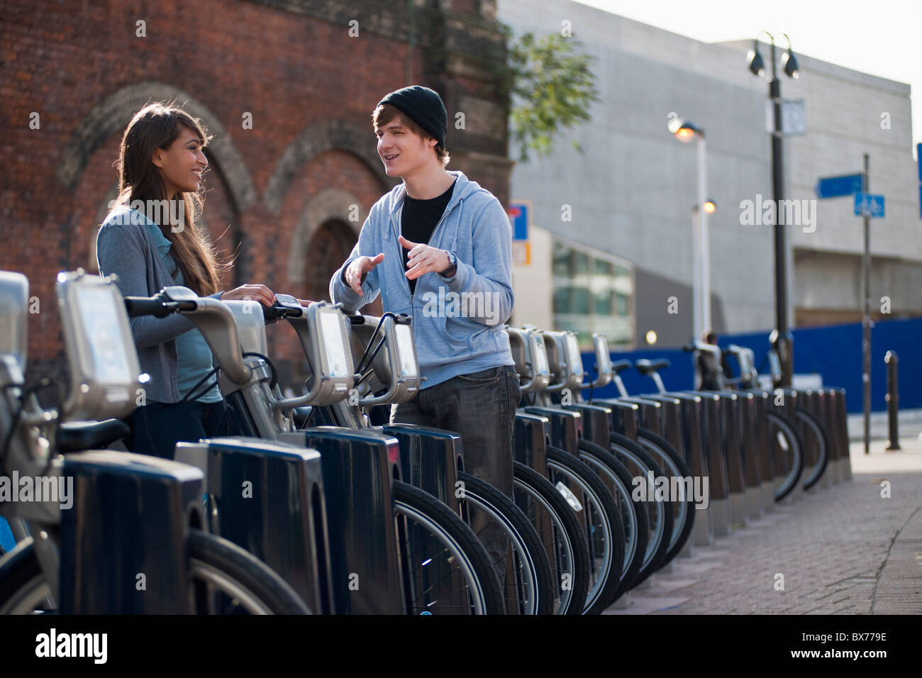 Young couple talking with rented bicycle - Stock Image