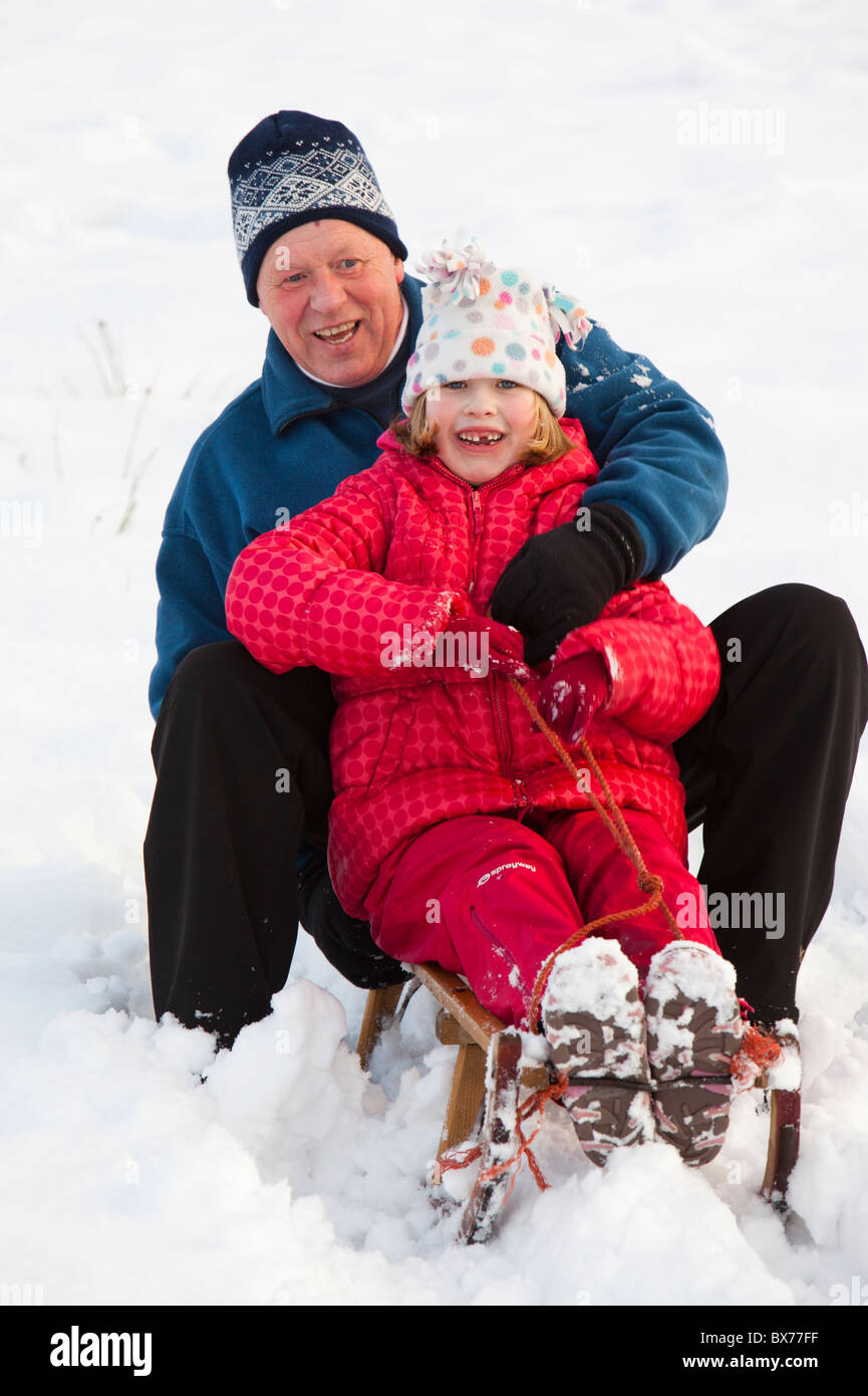 A grandfather sledging with his grand daughter in Ambleside, Lake District, UK. - Stock Image