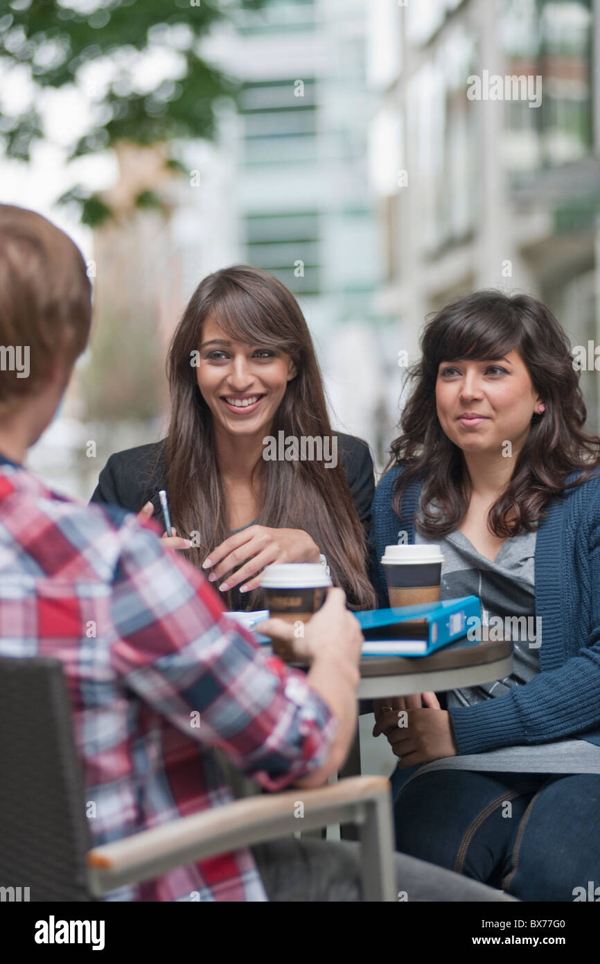 3 friends seated at cafe table Stock Photo
