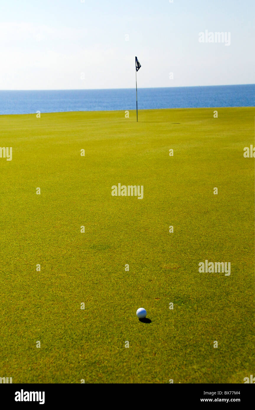 Golf ball on putting green with flag pole and Pacific Ocean at Puerto Los Cabos Golf Club in San Jose del Cabo, - Stock Image
