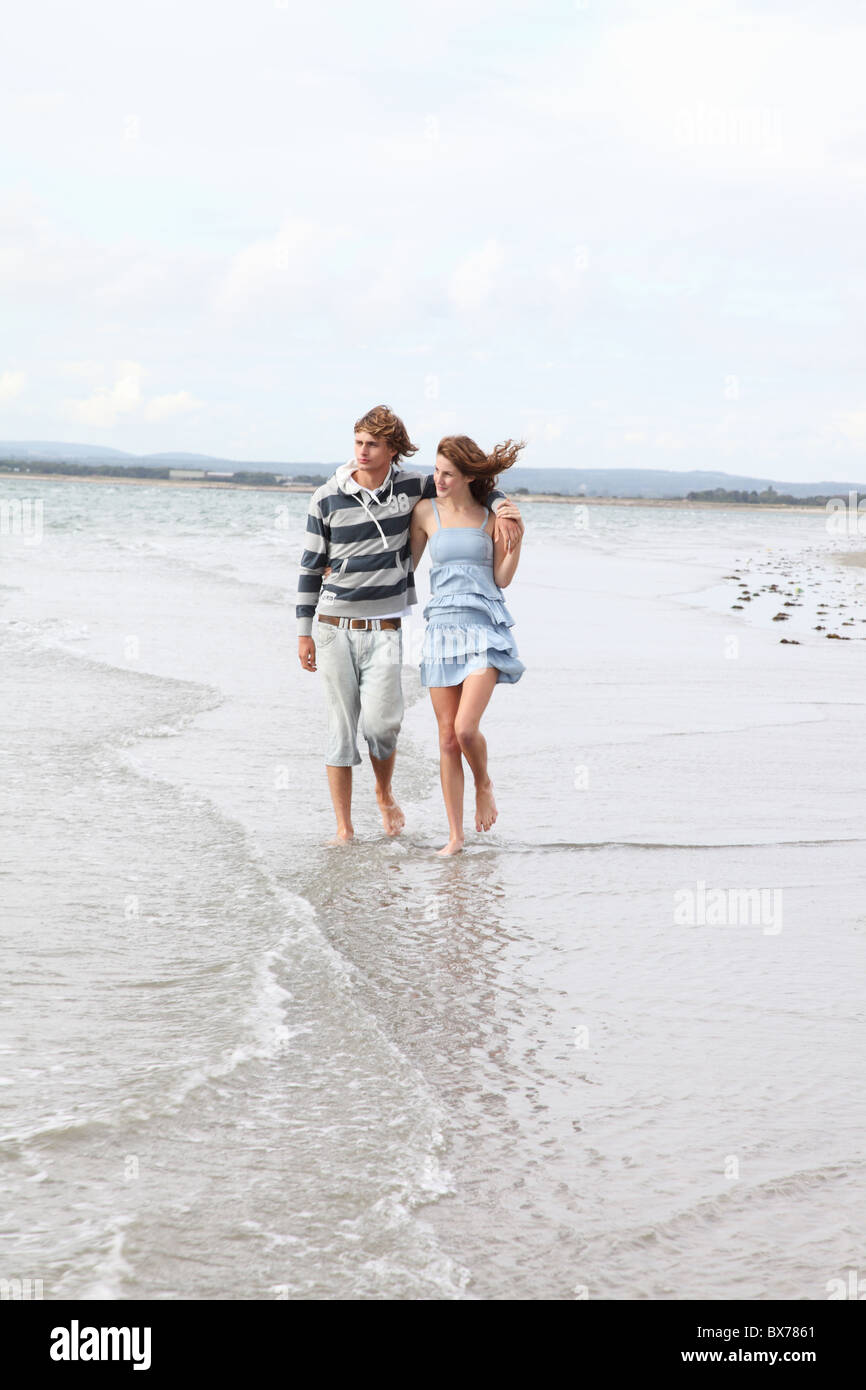 A  couple take a romantic beach stroll - Stock Image