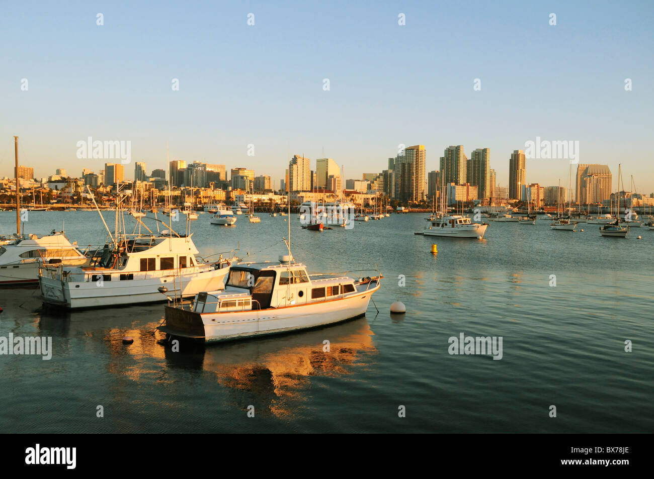 San Diego yacht harbor and bay with boats moored and anchored below city skyline at sunset - Stock Image