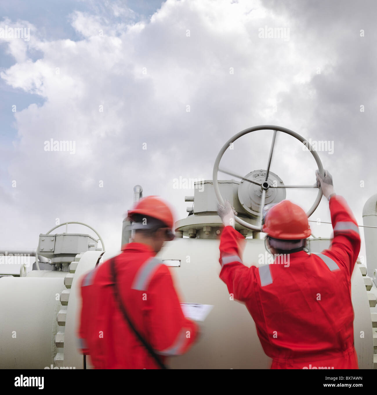 Workers with valve at gas storage plant - Stock Image