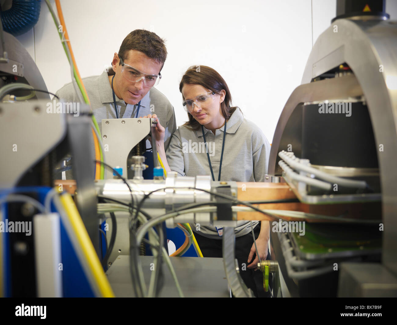 Scientists with particle accelerator - Stock Image