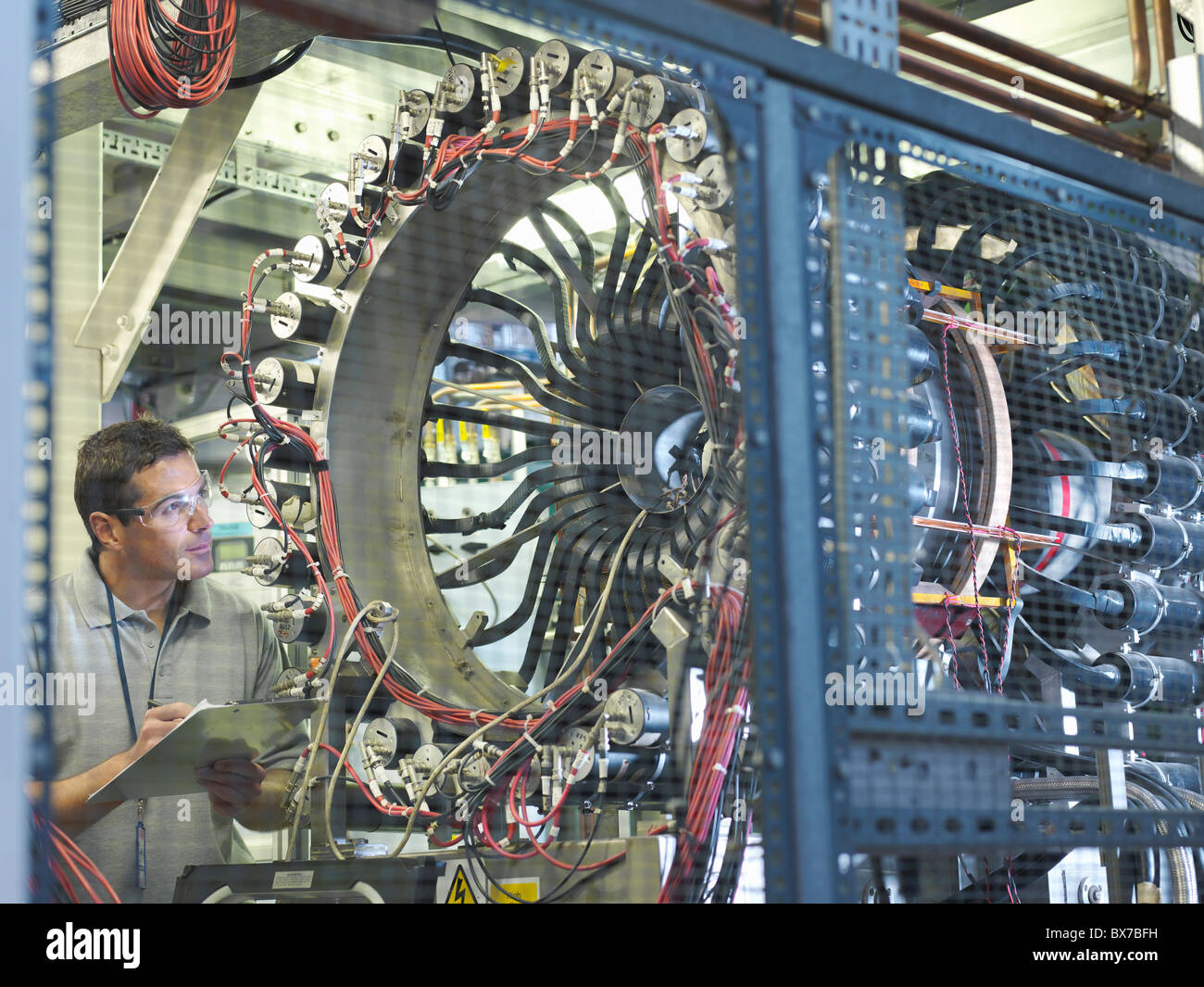 Scientist inspects particle accelerator - Stock Image