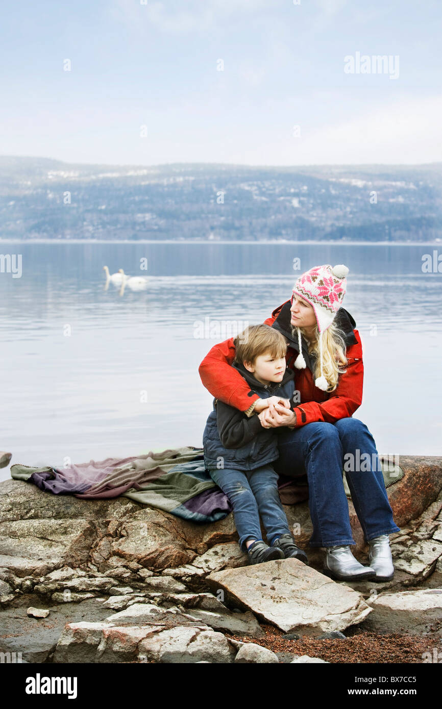Mother and son relaxing at lake - Stock Image
