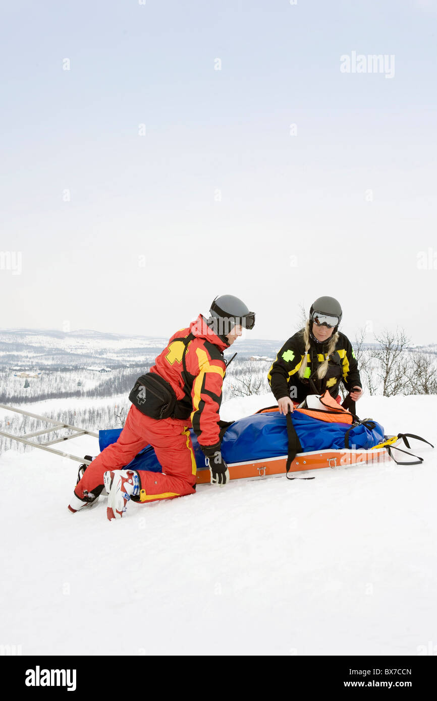 Two Rescuers helping skier - Stock Image