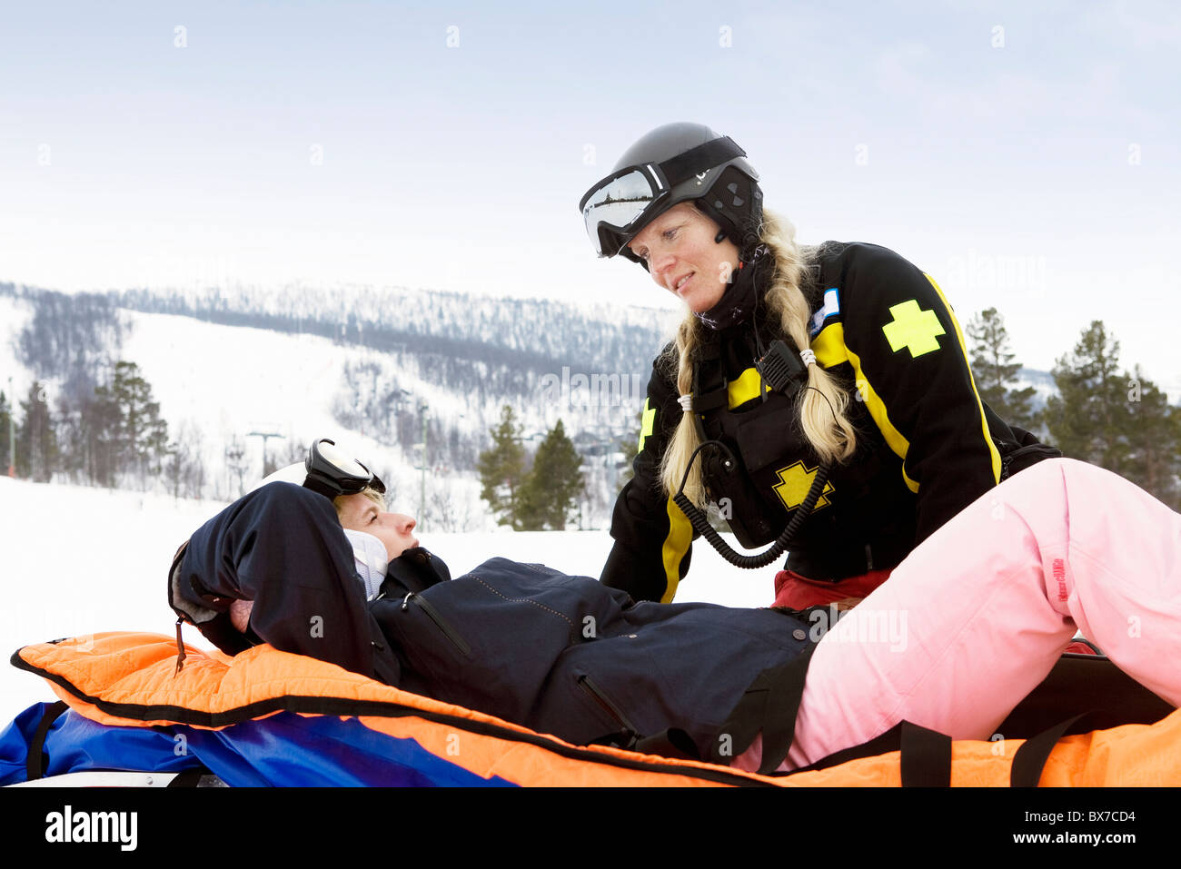 Woman Rescuer with Skier - Stock Image
