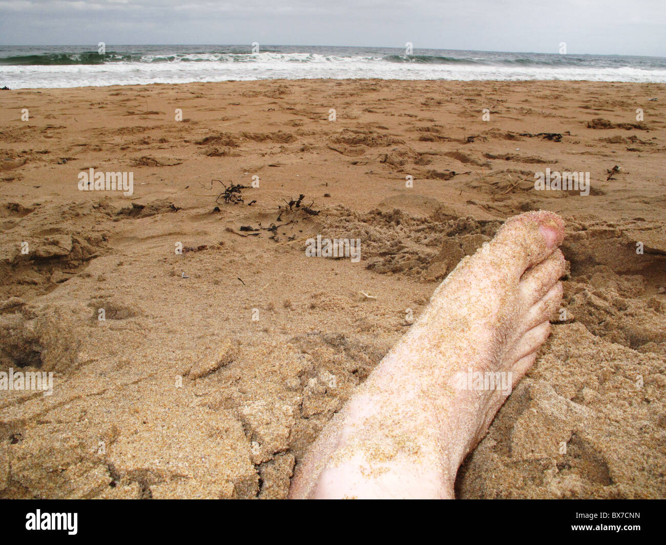 Mans foot on beach under dull sky - Stock Image