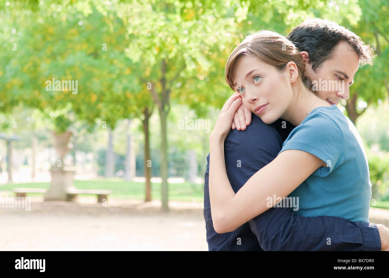 Couple embrace in park in Paris - Stock Image