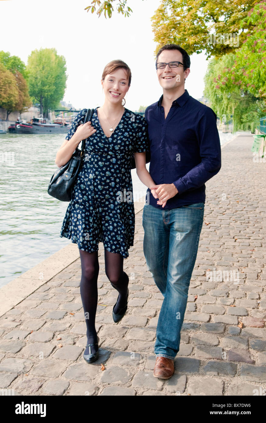 couple arm in arm by the Seine Paris - Stock Image