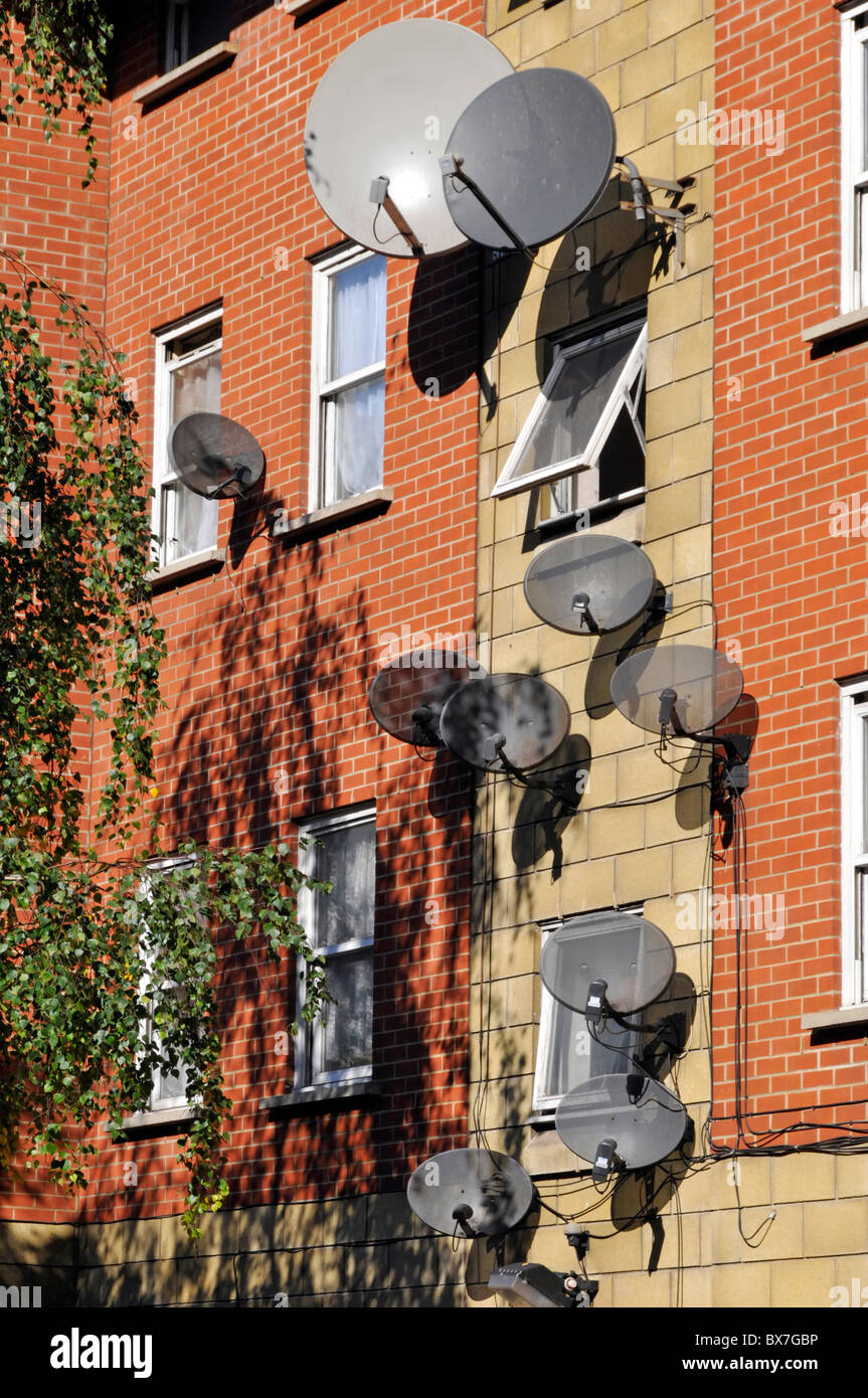 Large cluster of wall mounted TV satellite aerial dish installations  including Sky TV aerials on side of residential - Stock Image
