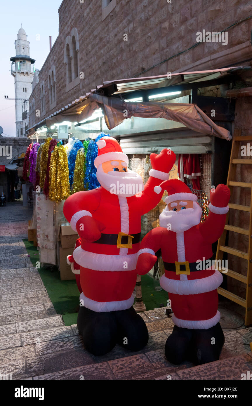 Inflatable santa klaus for sale in the Old City of Jerusalem with minaret in BKGD Stock Photo