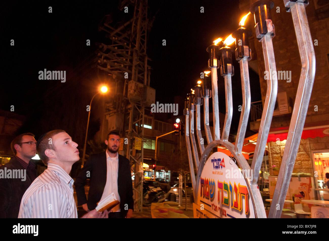 Lubavitch jews lighting a street hanukiah during the Jewish Hanukah festival. Jerusalem. israel - Stock Image