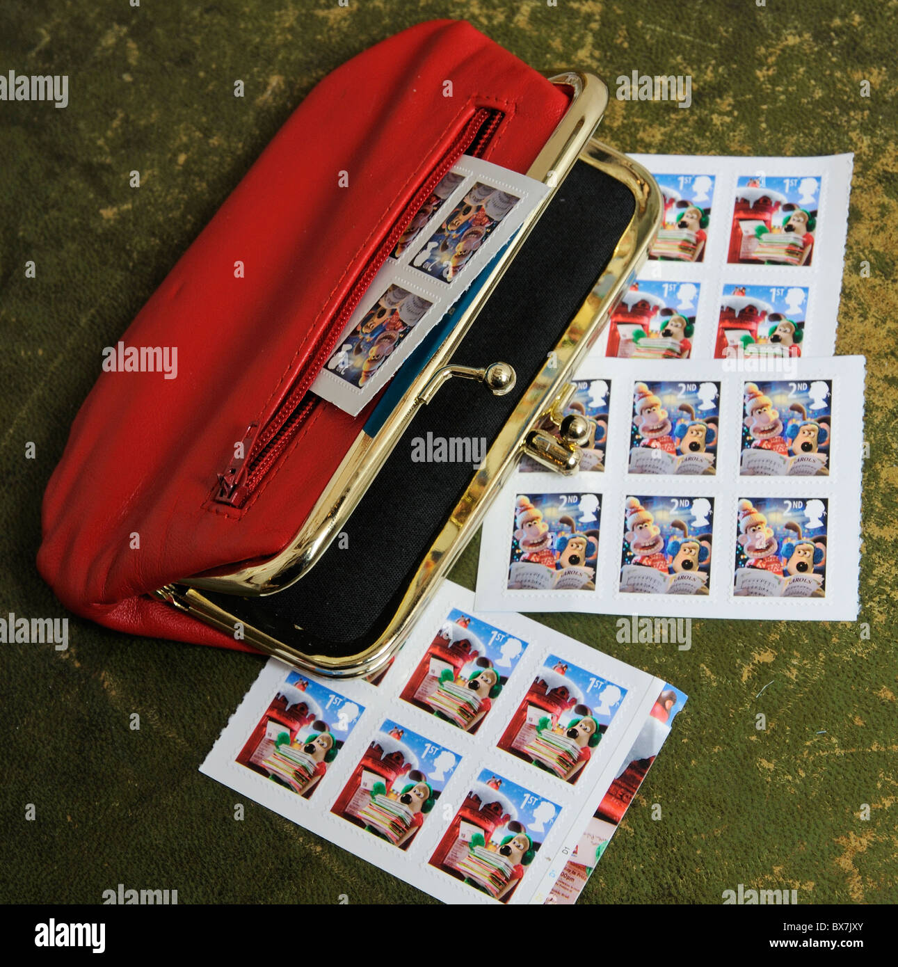 Red leather purse with Christmas theme British postage stamps - Stock Image