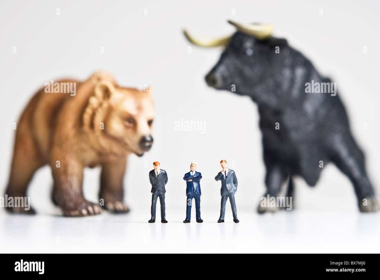 Business figurines placed with bull and bear figurines. Stock Photo