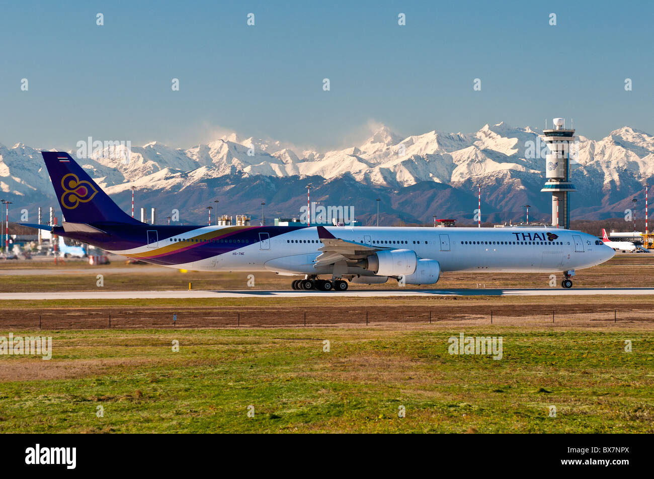 Thai airways' Airbus 340-600 ready for takeoff with the snowy Alps in the background, Milan Malpensa airport, - Stock Image