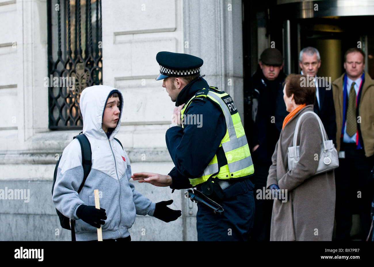 A Metropolitan police officer detaining a young male. - Stock Image