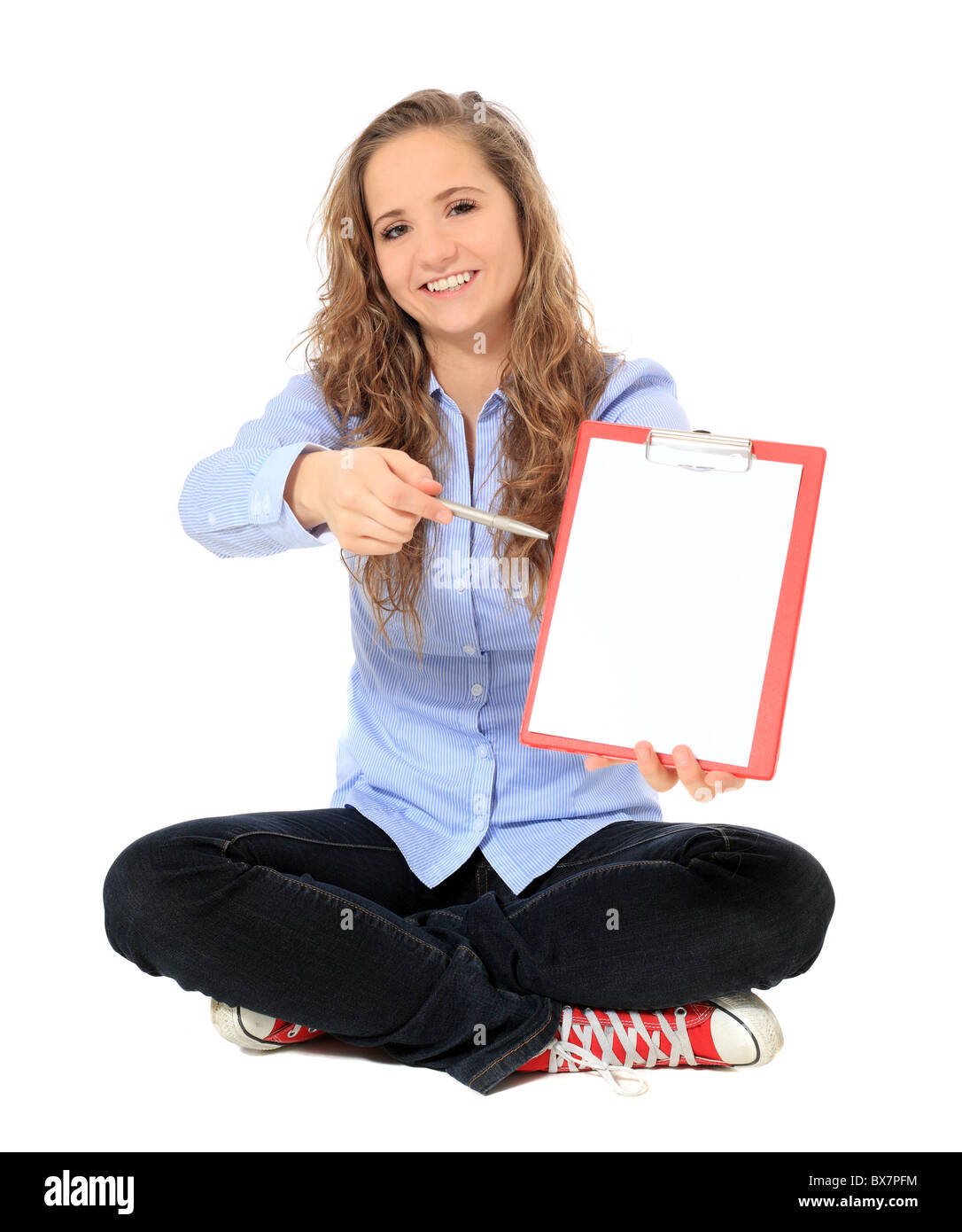 Attractive young girl pointing with pen on clipboard. All on white background. - Stock Image
