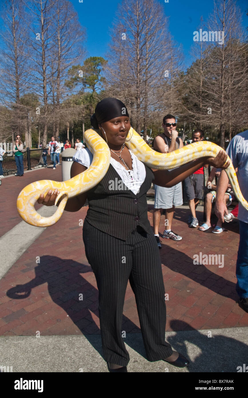 Lady with large yellow snake at street fair in Orlando, Florida - Stock Image