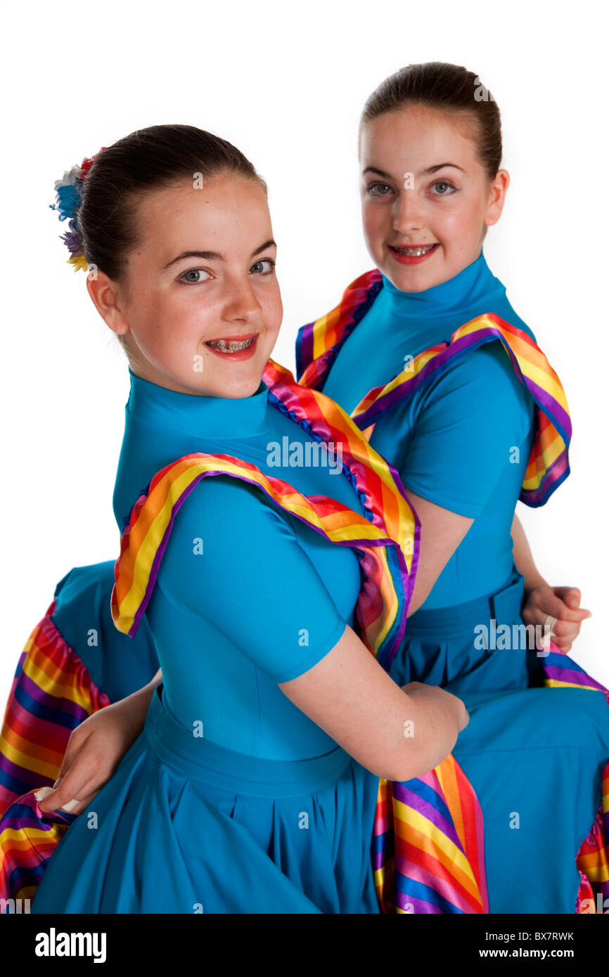 Studio shot of beautiful young identical twins in colourful Mexican national dancing costume - Stock Image