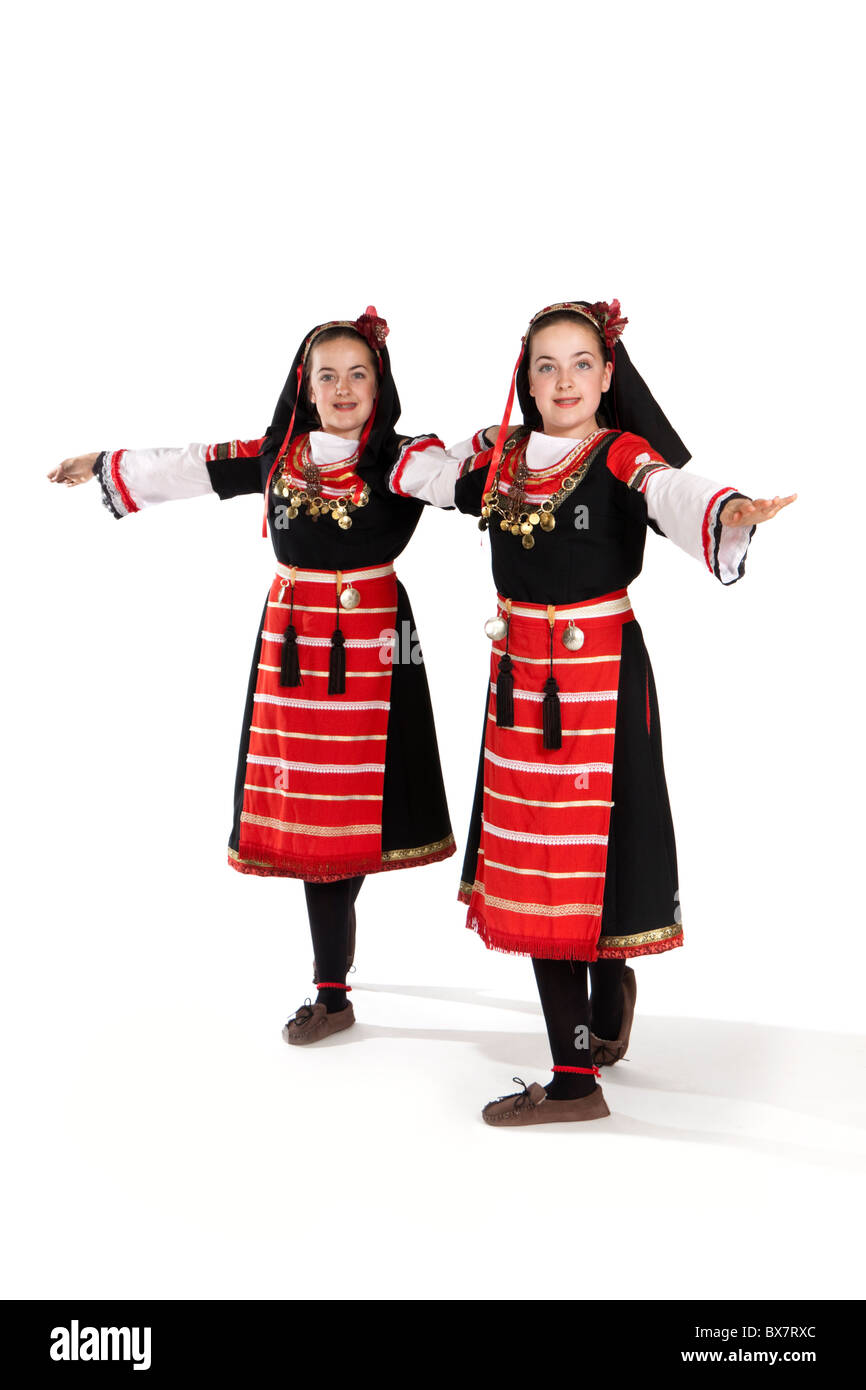 Studio shot of beautiful young identical twins in colourful Romanian national dancing costume - Stock Image