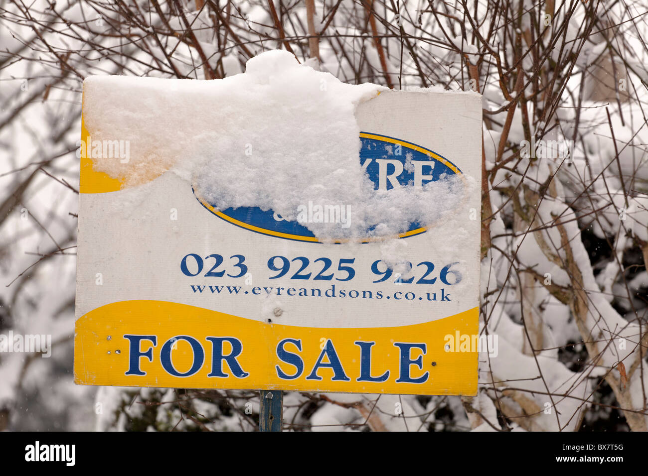 house for sale board partially obscured by snow - Stock Image
