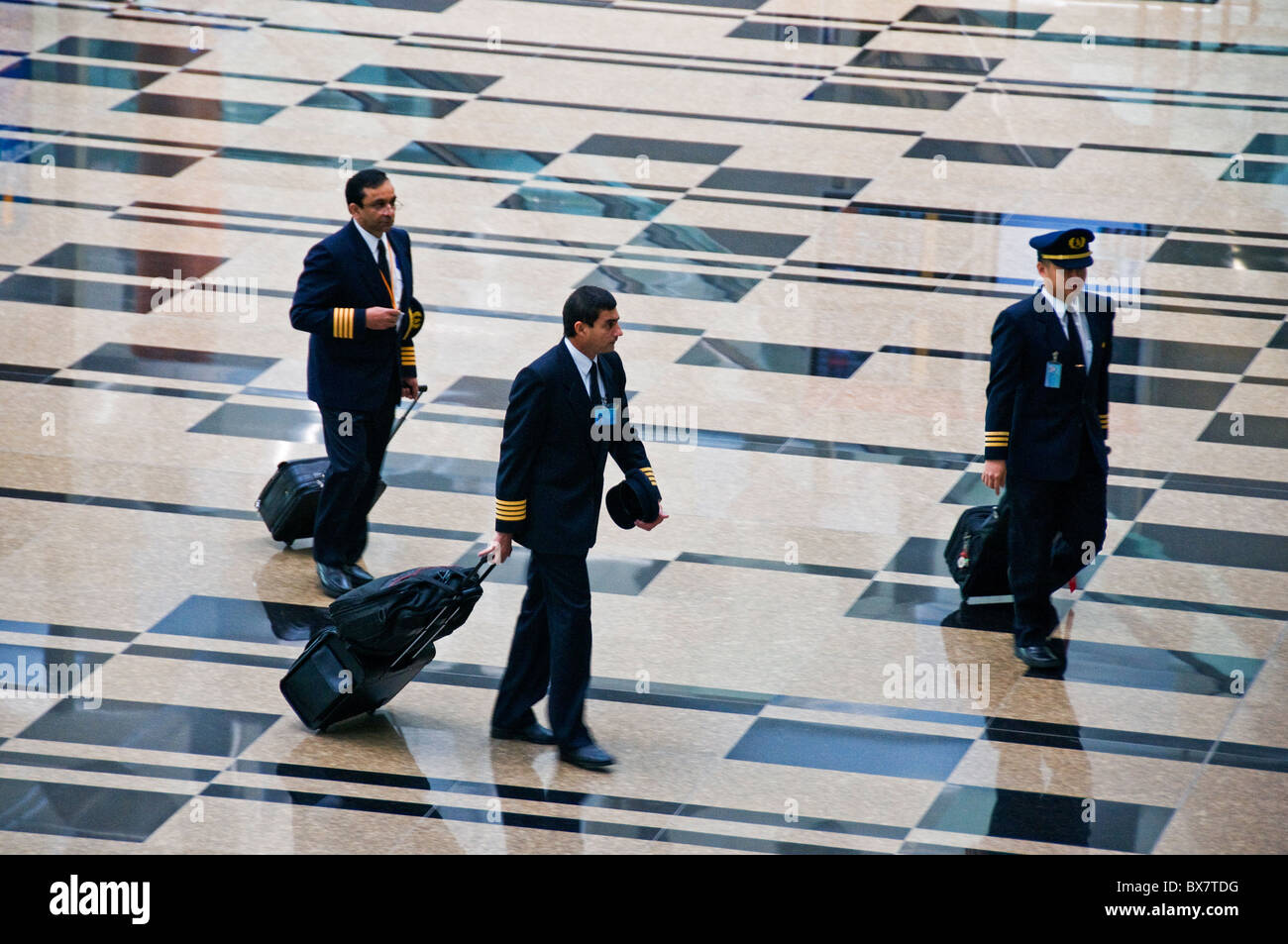 Pilots walking in Interior of new modern Changi airport terminal in Singapore southeast Asia - Stock Image