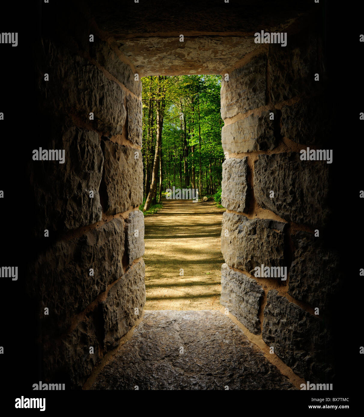 Path through trees as viewed out of a castle-like stone window or passage - Stock Image