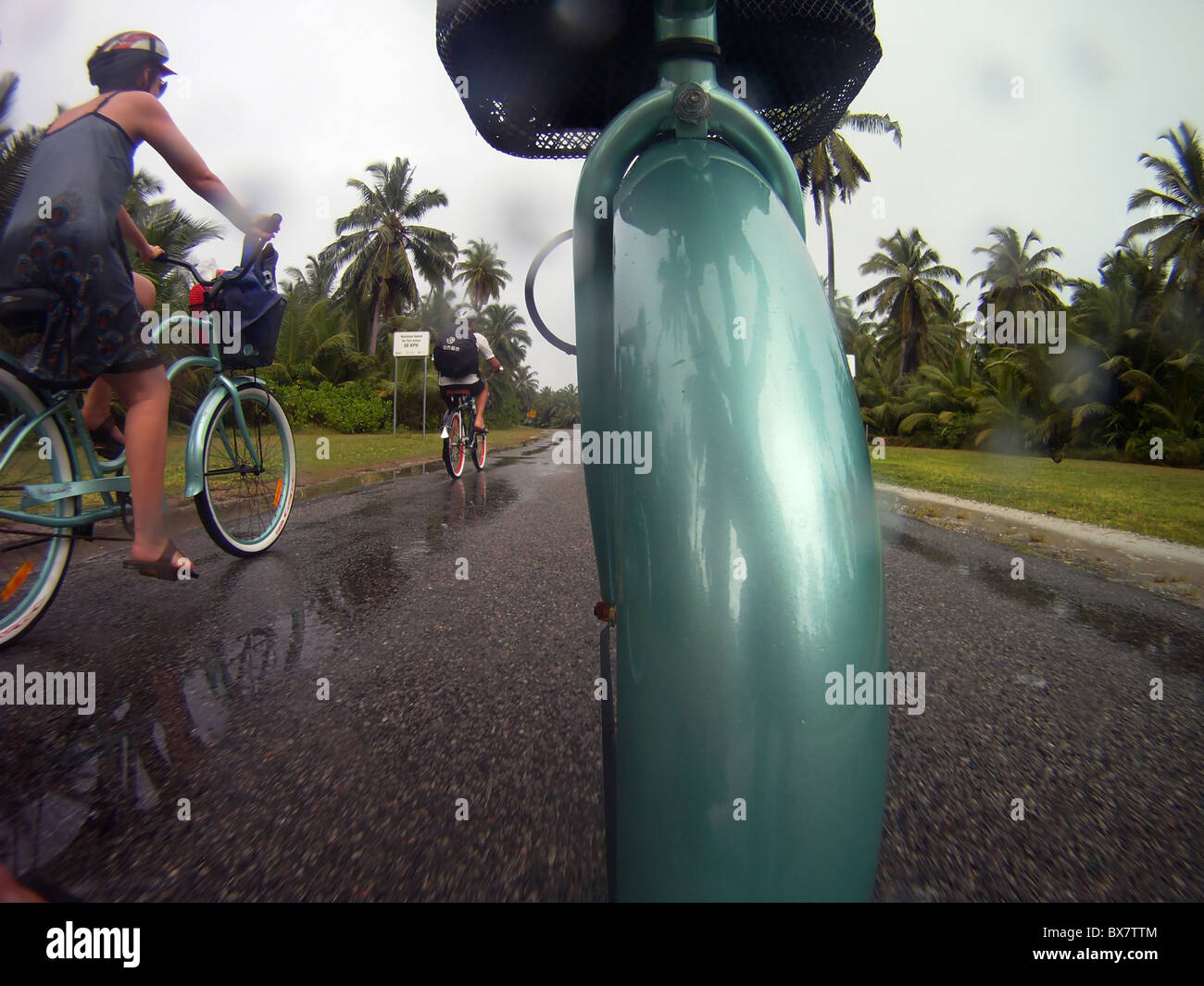 Tourists cycling in the monsoon, West Island, Cocos Keeling, Indian Ocean Stock Photo