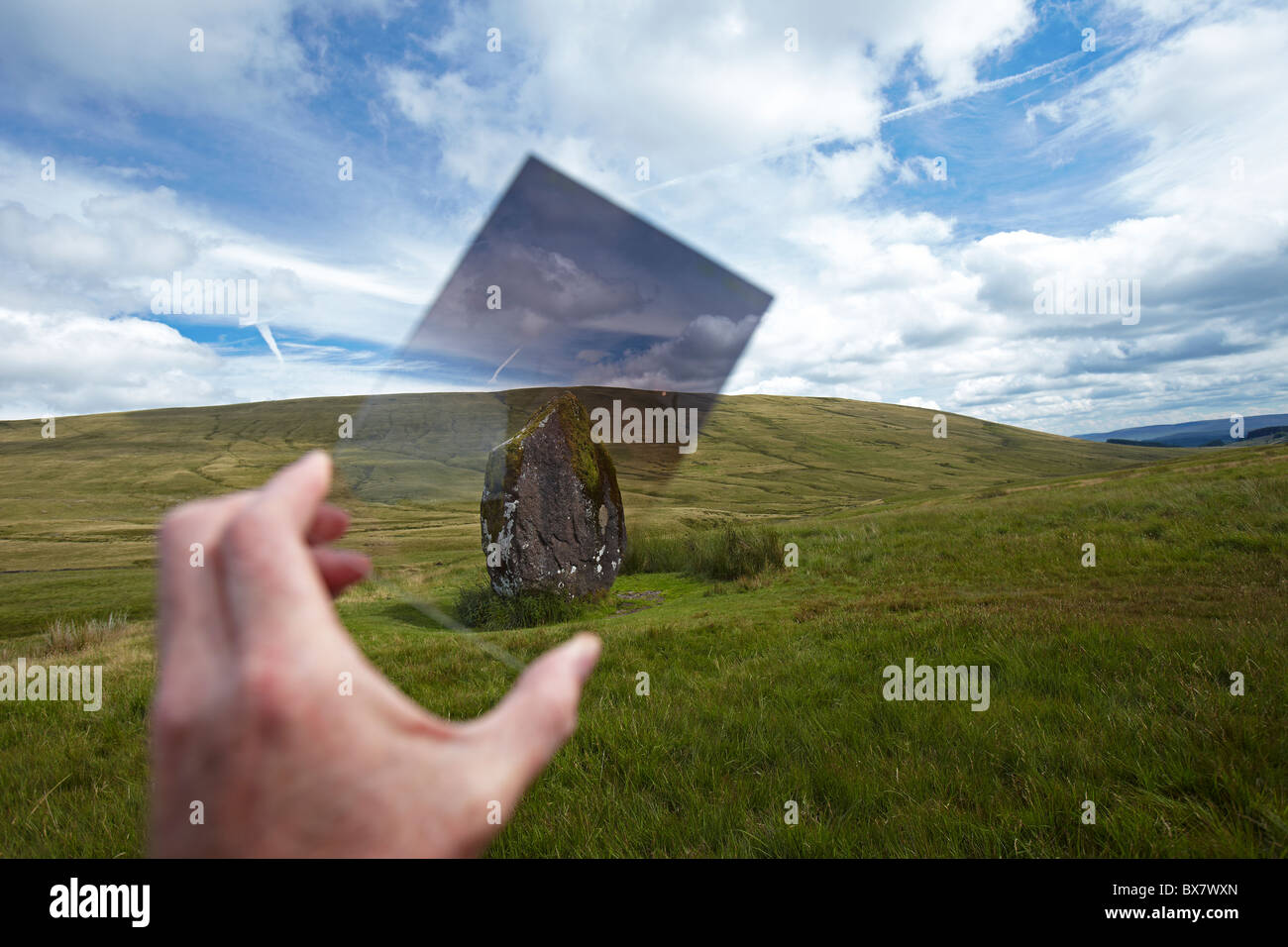 Photographer holding a graduated filter in front of the Neolithic Monument Maen Llia, Brecon Beacons, Wales, UK - Stock Image