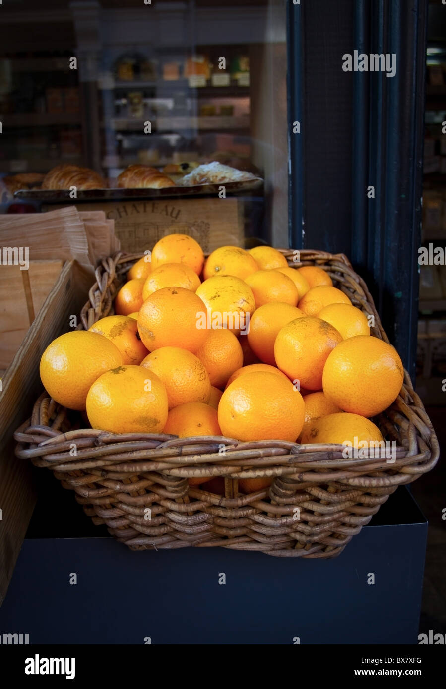 Basket of oranges in shop window stall - Stock Image