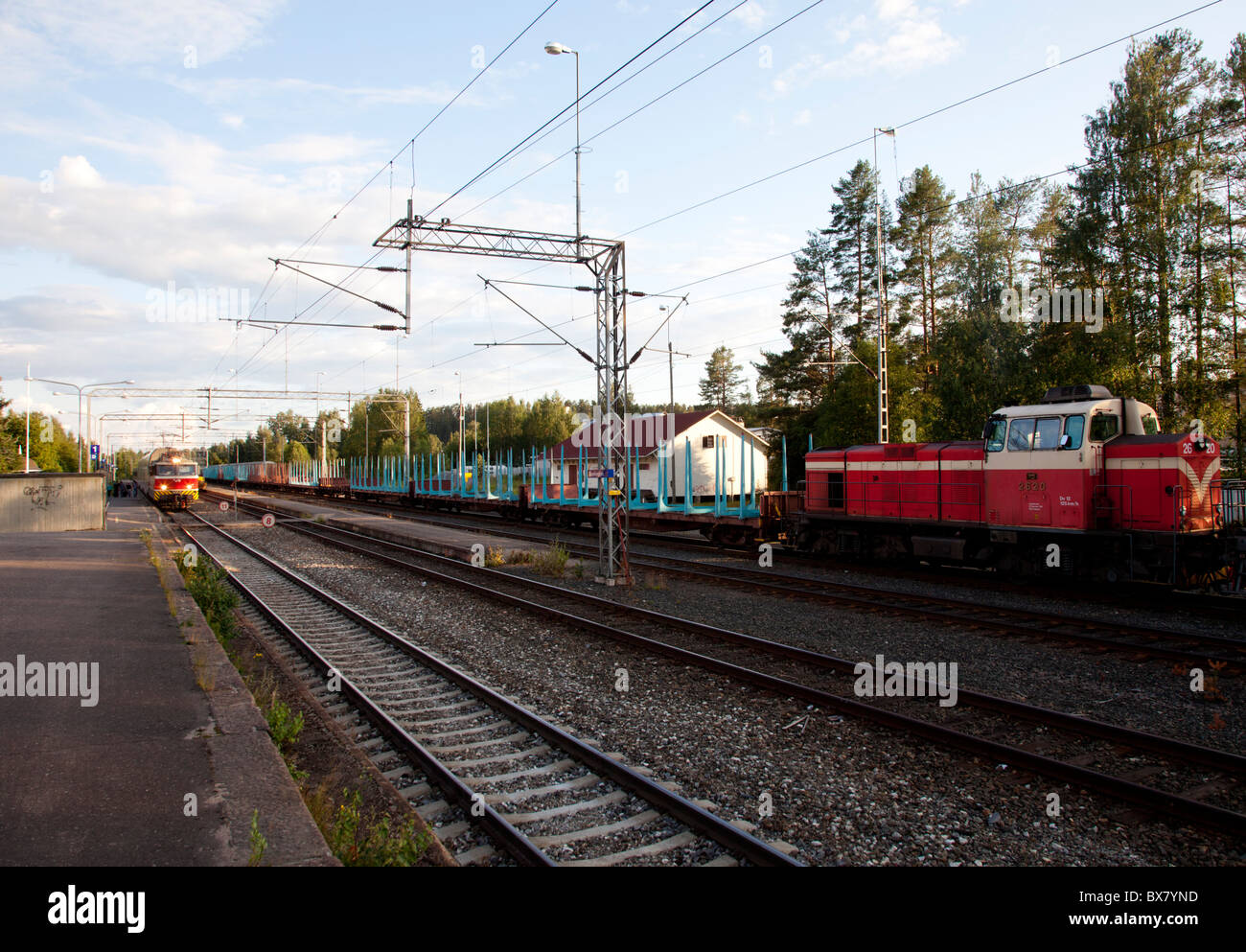 Railway station and cargo train waiting for the oncoming passenger train to pass it , Finland - Stock Image