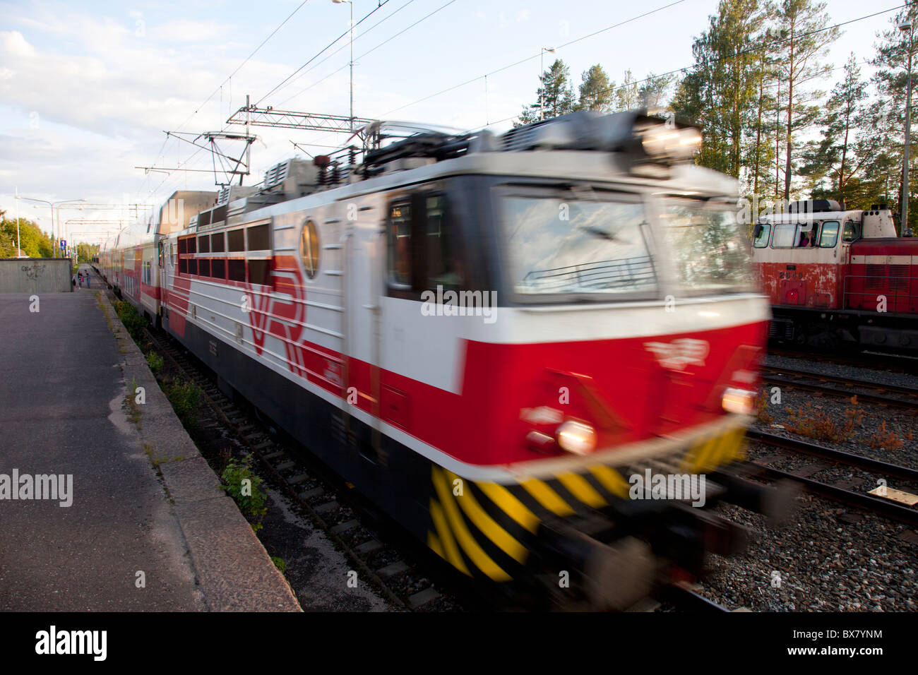 Passenger train with electric locomotive leaving railway station , Finland - Stock Image