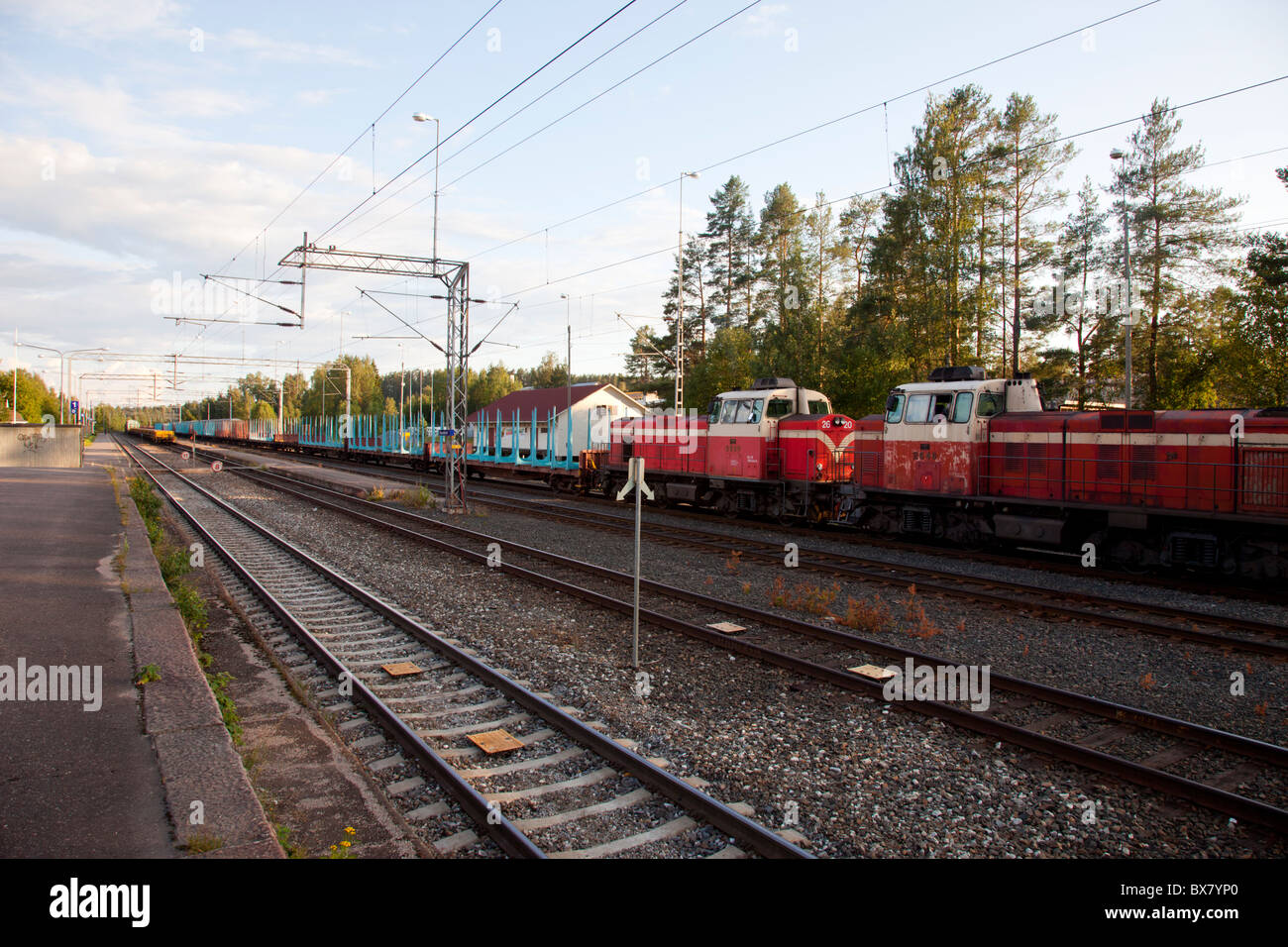 Railway station and empty cargo train , used to transport logs, powered by two diesel electric locomotives , Finland - Stock Image