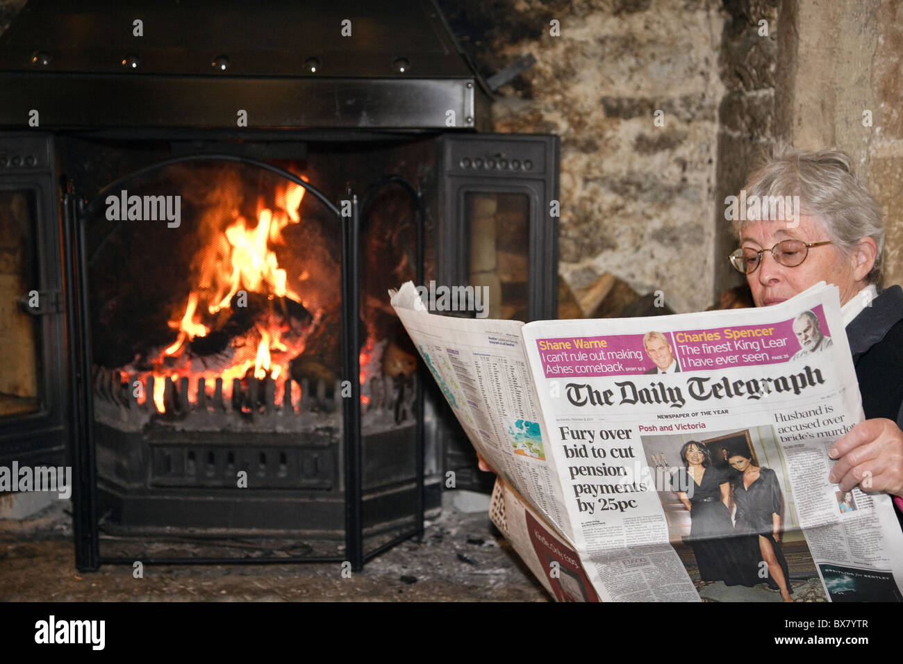 Senior woman pensioner retiree reading a Daily Telegraph broadsheet newspaper reporting pension cuts by an open - Stock Image