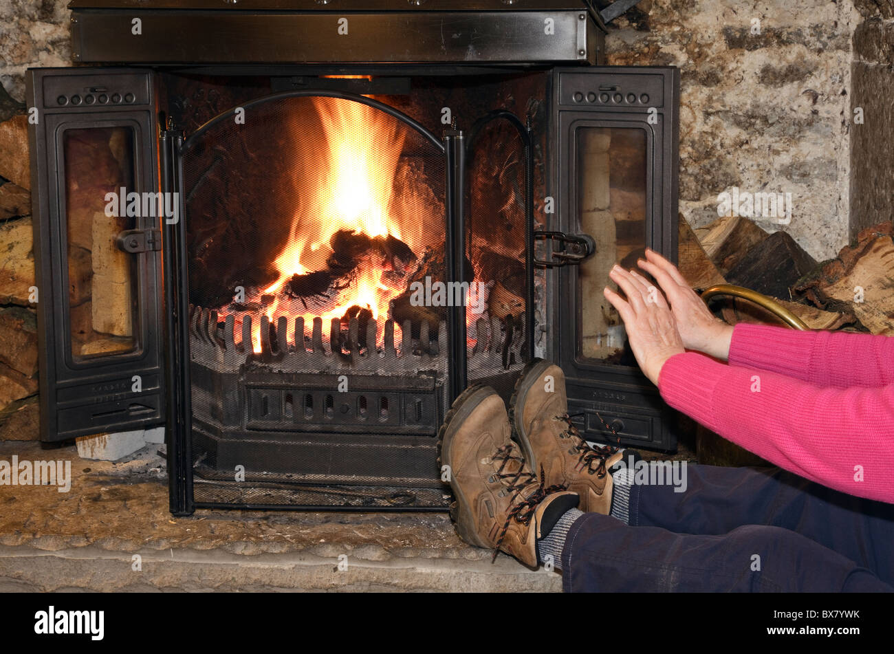 England, UK. Person wearing boots warming cold hands and feet sat in front of an open log fire at home - Stock Image
