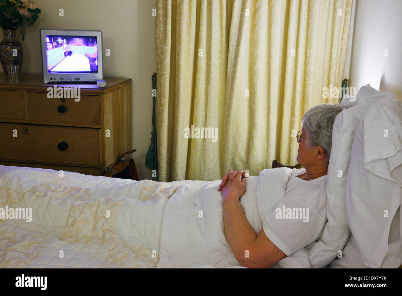 Elderly woman retiree lying in bed watching television in a hotel bedroom relaxing on holiday. England, UK, Britain. - Stock Image