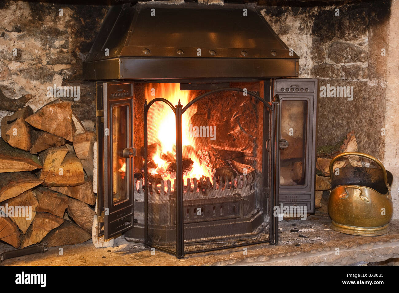 Open log fire with logs burning and fireguard on the hearth in cosy warm domestic living room. England, UK, Britain - Stock Image