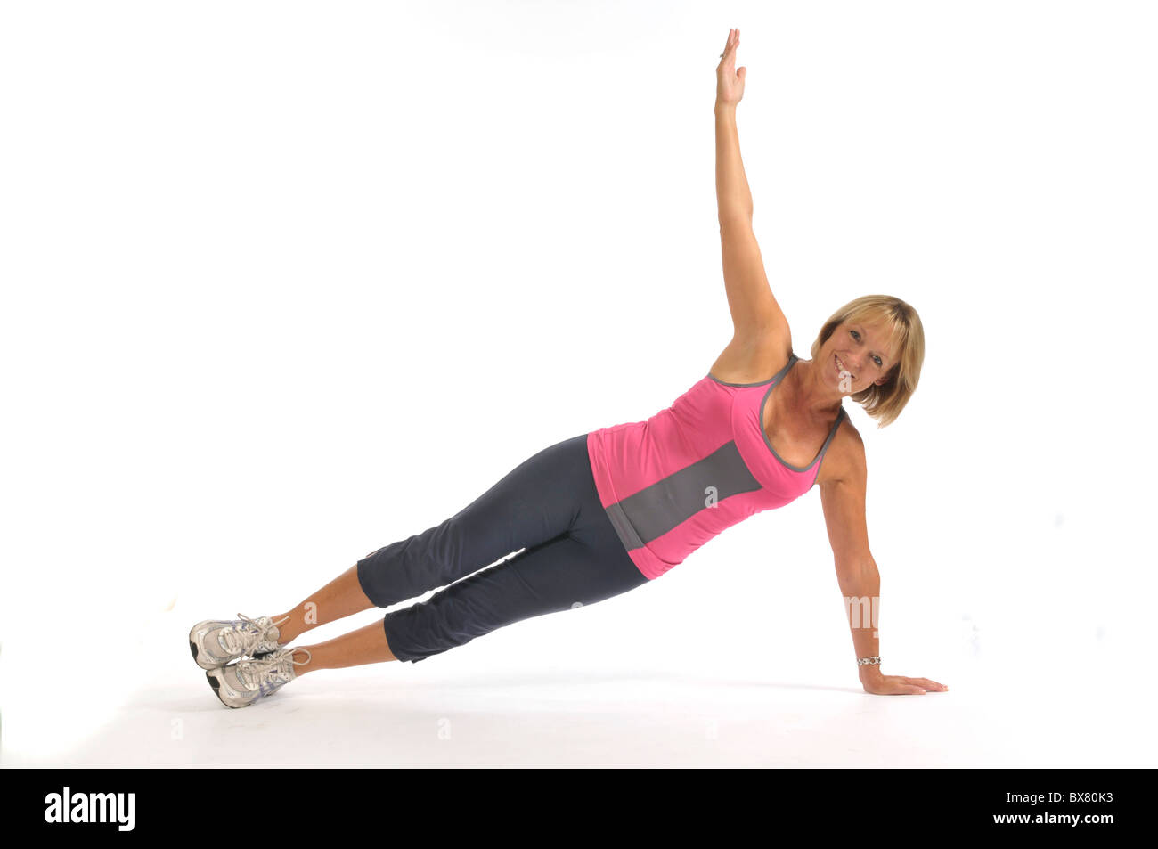 50 yr old female demonstrating side plank in studio - Stock Image