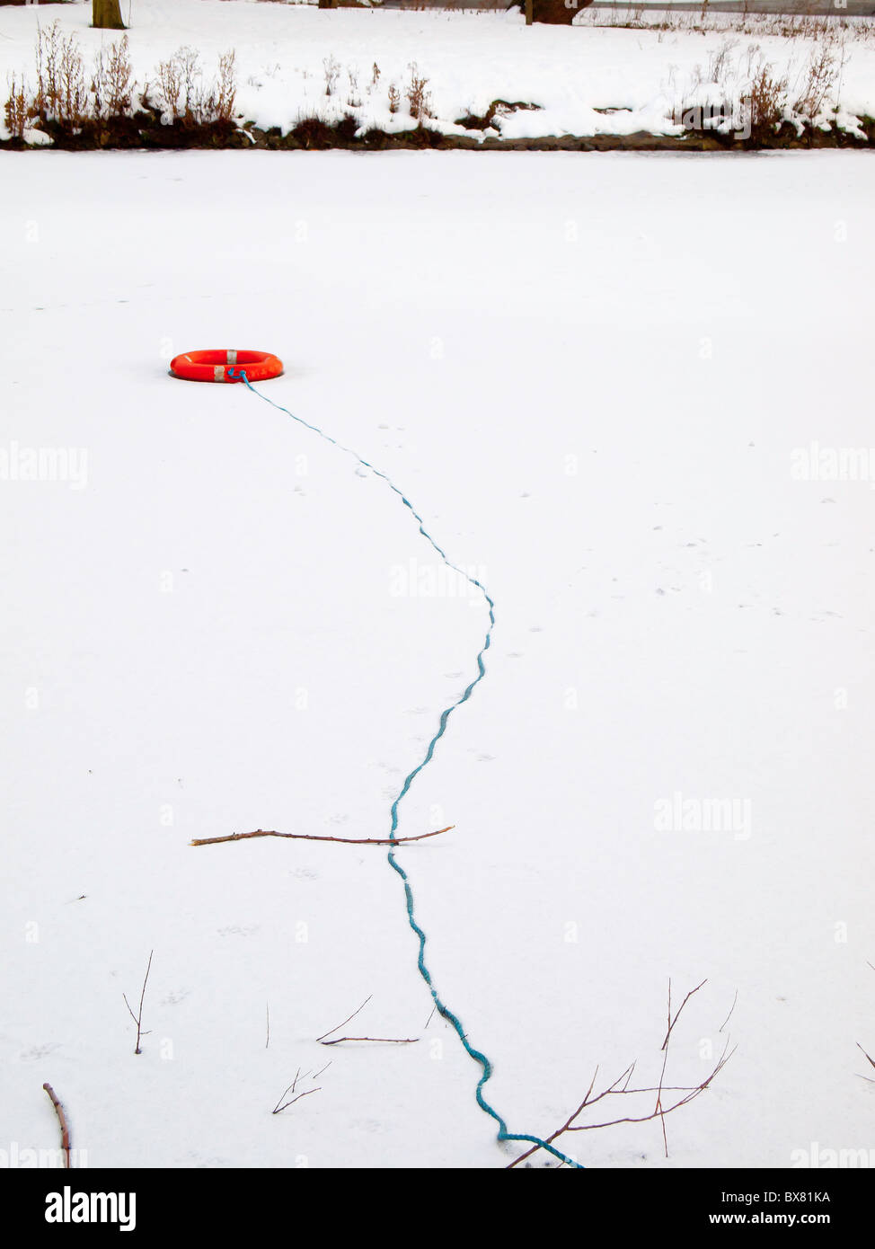 A lifebuoy thrown out on an ice and snow covered lake by vandals - Stock Image