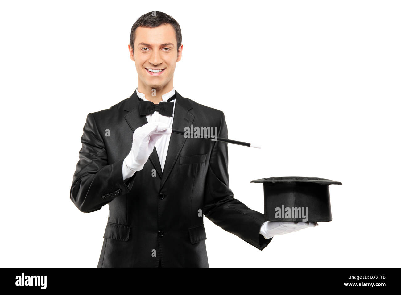 A magician in a black suit holding an empty top hat and magic wand - Stock Image