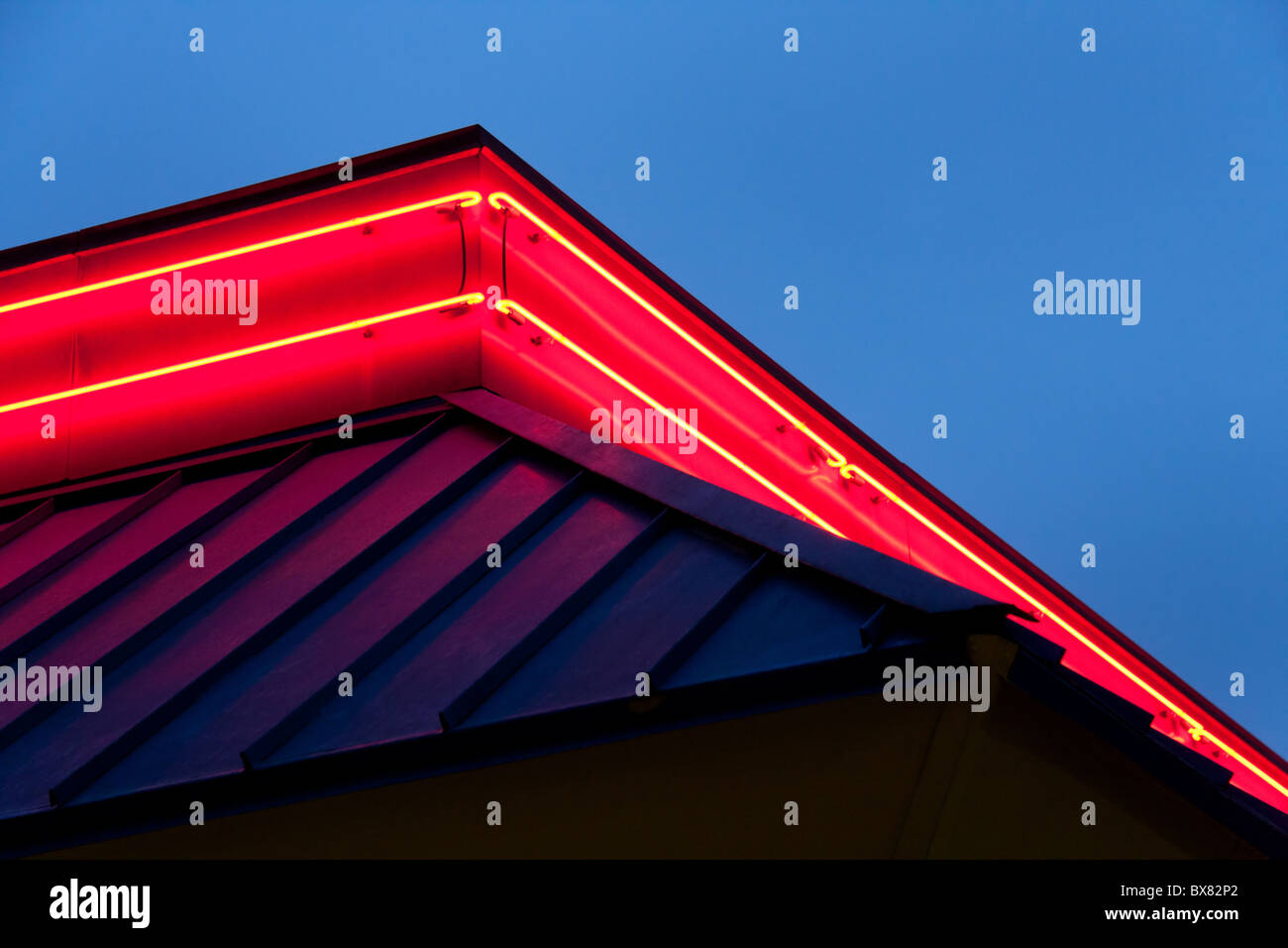 Neon lights on fast food restaurant building - Stock Image